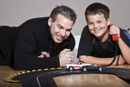 Father And Son Playing With Toy Race Track