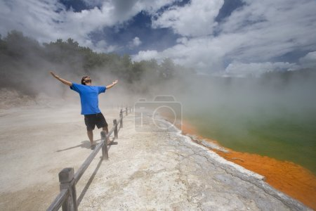 Man At Champagne Pool At Geothermal Site, Wai-O-Tapu Thermal Wonderland On North Island Of New Zealand