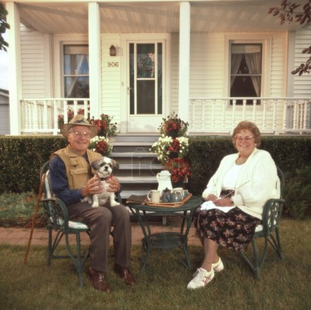 Senior Couple Relaxing In Front Of House
