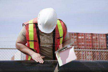 Photo pour Homme inspectant le tuyau - image libre de droit
