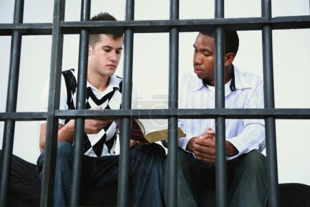 Young Man Reads The Bible To Another Young Man In Jail