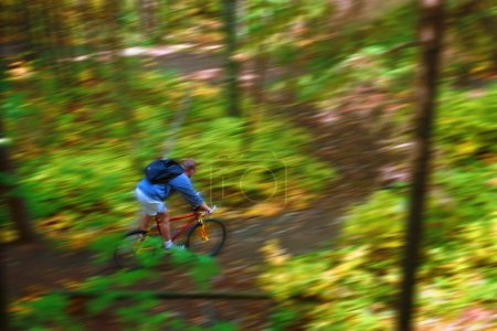 Man Cycling Down Forest Trail