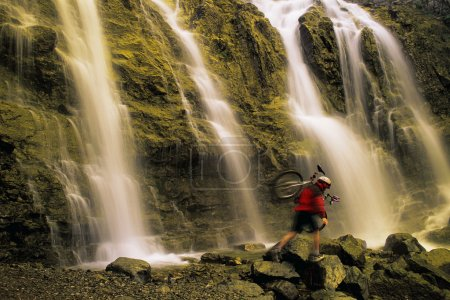 Time Delay Of Waterfall With Cyclist Carrying Bicycle