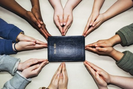 Praying Hands Pointing To A Bible