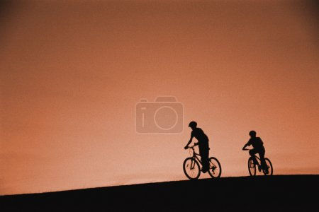 Silhouette Of Cyclists On Hill