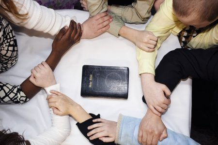 Group Of People Praying Around A Bible