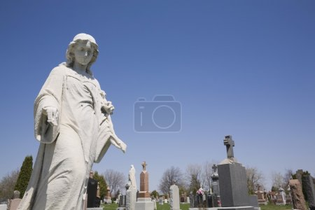 Statue And Headstones In Cemetery