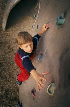 Little boy climbing wall
