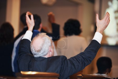 Man Sitting In Church With Hands Raised