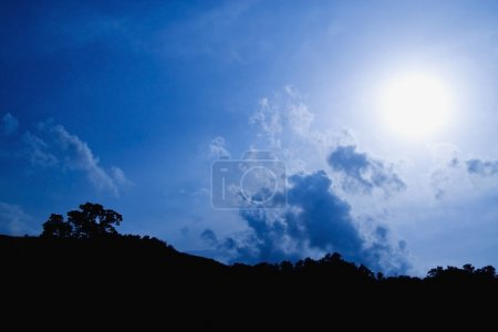 Photo for Sun Shining Through Blue Clouds - Royalty Free Image