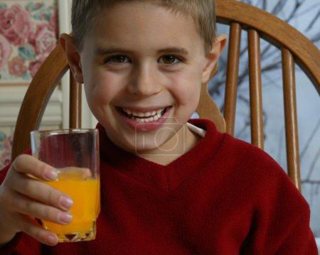 Young Boy Smiling And Holding Orange Juice