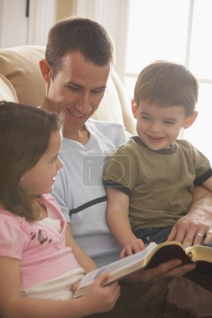 Father Reading The Bible To His Young Son And Daughter