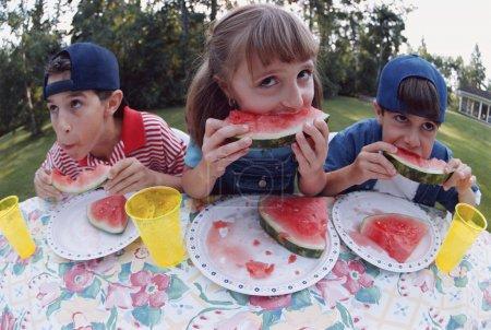 Photo pour Trois enfants mangent de la pastèque à une table de pique-nique - image libre de droit