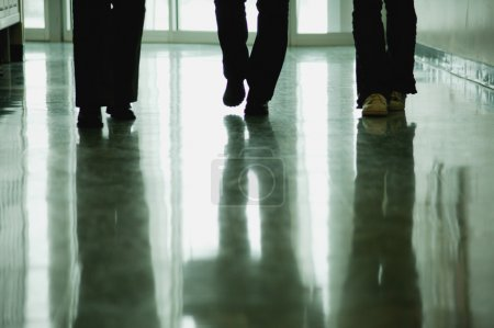 People Walk Down Hallway