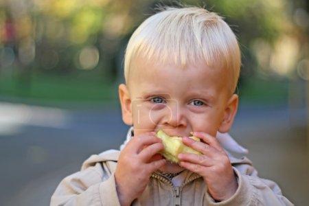 A boy bites into an apple