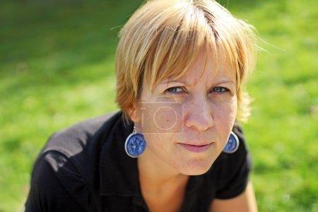 Photo pour Une femme qui regarde sérieusement avec des boucles d'oreilles - image libre de droit