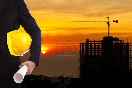 Construction engineer holding yellow helmet for workers security on background of new highrise apartment buildings