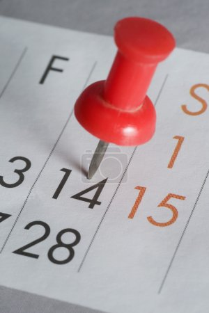 Close-up of a thumbtack on the 14th date of a calendar