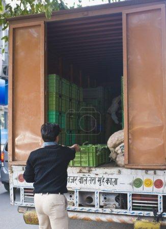Men unloading vegetables in a truck