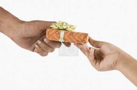 Man's hand giving a gift box to a woman