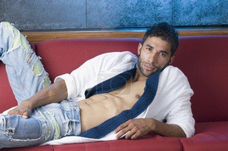 Macho man lying on a couch