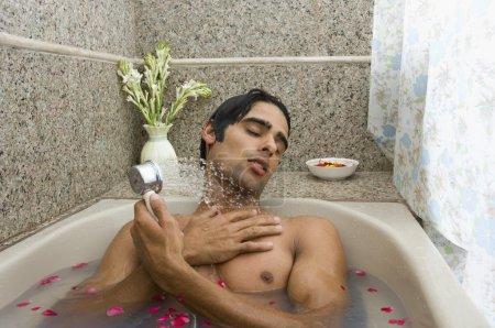 Mann duscht in Badewanne