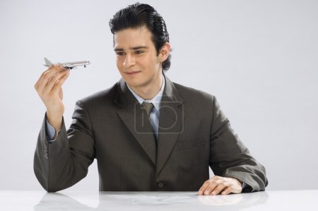 Businessman holding a model airplane
