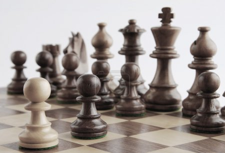 White pawn facing black chess pieces