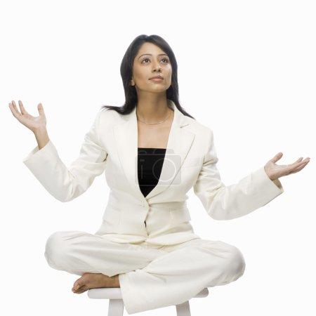 Businesswoman meditating on a stool