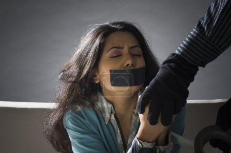 Foto de Manos del secuestrador envolviendo cinta adhesiva alrededor de las manos de una mujer joven secuestrada - Imagen libre de derechos