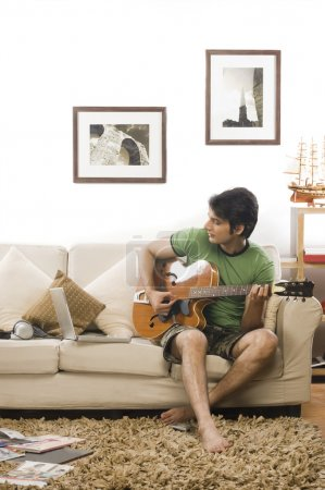 Man playing a guitar in the living room