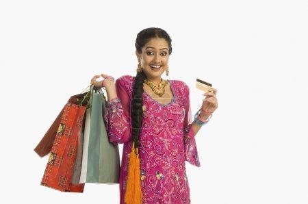 Photo pour Heureuse femme tenant des sacs à provisions avec une carte de crédit - image libre de droit