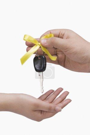 Main donnant une clé de voiture à une autre personne
