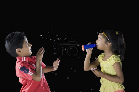 Girl blowing bubbles towards a boy