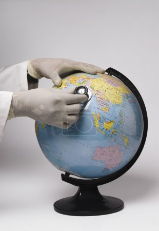 Hands examining a globe with a stethoscope