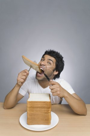 Man eating a slice of bread