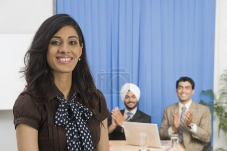 Photo for Businesswoman smiling with her colleagues in the background - Royalty Free Image