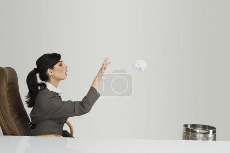 Businesswoman throwing crumpled paper