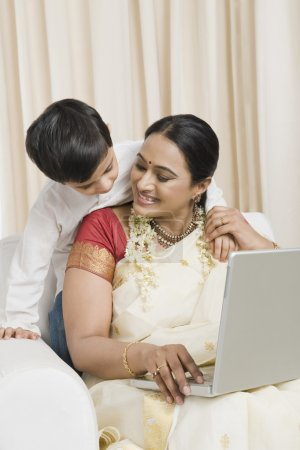 Woman using a laptop with her son