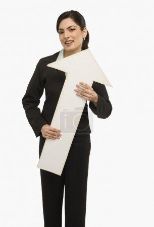 Businesswoman holding an upward arrow sign