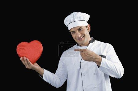 Photo pour Chef pointant vers un cadeau en forme de coeur - image libre de droit