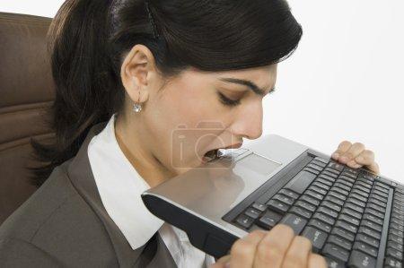 Businesswoman biting a laptop