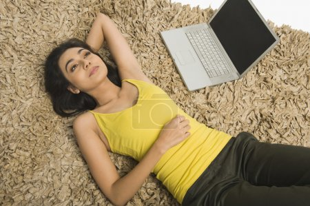 Woman lying on a rug with a laptop