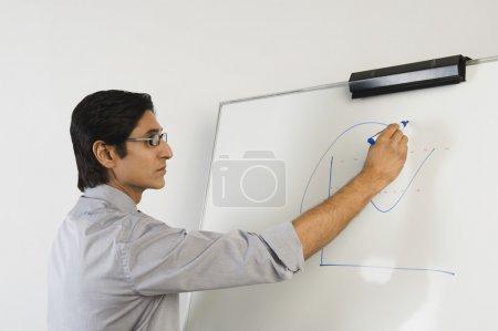 Photo pour Professeur écrivant sur un tableau blanc - image libre de droit