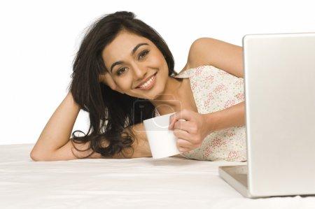 Woman lying on the bed with coffee mug