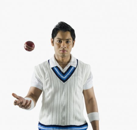 Cricket bowler tossing a ball