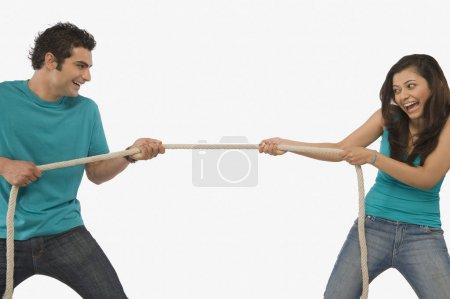 Young couple playing tug of war