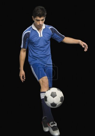 Photo for Soccer player practicing with a soccer ball against black background - Royalty Free Image