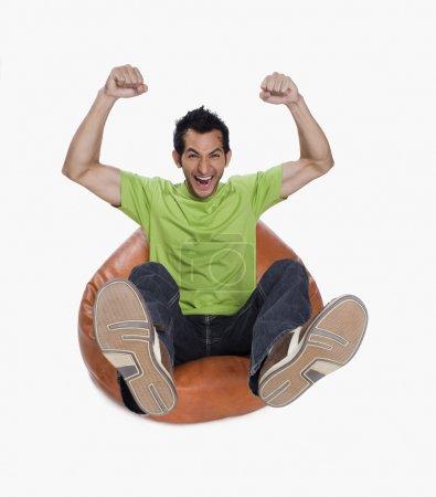 Man cheering on a bean bag