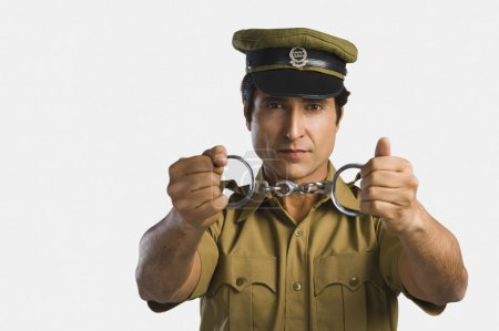 Policeman holding a pair of handcuffs